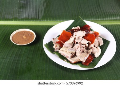Chopped parts of the delicacy lechon or suckling pig on a banana leaf. The food is popular in Spain and former Spanish colonial regions