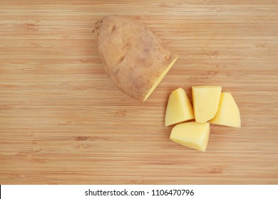 Chopped potatoes on wood board. Top view.