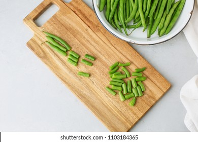 Chopped Raw Green Beans on a Wooden Cutting Board against a Gray Background; Top view