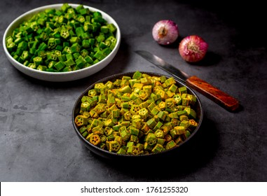 chopped raw okra mixed with turmeric powder in a bowl, preparation for indian vegetable bhindi fry