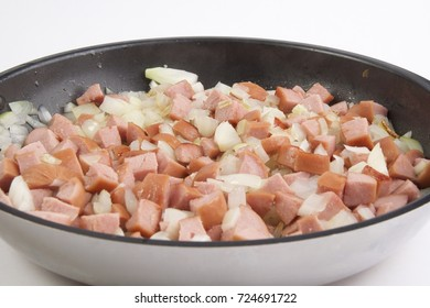 Chopped sausages and onions in a frying pan