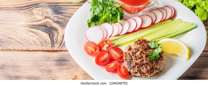 Chopped steak cutlet cooked on grill on white plate with assorty mix vegetables radish cherry tomatoes slices of cucumbers parsley lemon and sauce ketchup Concept food summer homemade picnic barbecue.