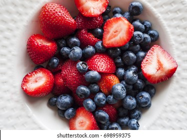 Chopped strawberries and blueberries in a while bowl.