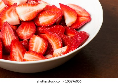 Chopped strawberries in a white bowl over a wooden background