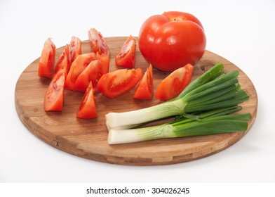 Chopped tomatoes and onions on a kitchen board.