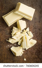 Chopped white chocolate on rusty background.