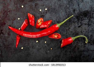 Chopped and whole рods of red chili peppers on a dark background close-up - top view