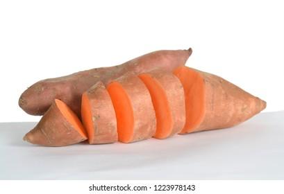 Chopped and whole sweet potato on white
