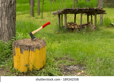 Chopper inserted into an old chopping block on a lush green campsite with scattered wood chips from chopping the wood for the barbecue and an old rustic lean-to visible behind, no people