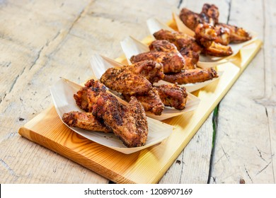 Chopping board with portion of chicken wings grilled in trays
