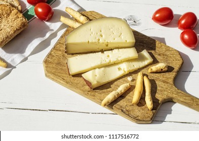 Chopping board with slices of asiago cheese and bread sticks on white wooden table (top view)