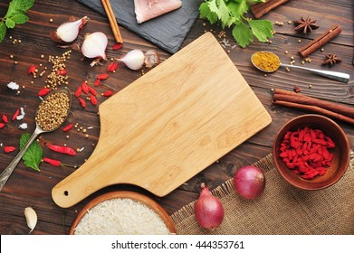 Chopping board with spices on wooden table.