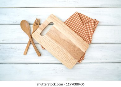 a chopping board and tablecloth with wooden fork and spoon on white table , recipes food  for healthy habits shot note background concept