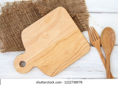chopping board and tablecloth with wooden fork and spoon on white table , recipes food  for healthy habits shot note background concept