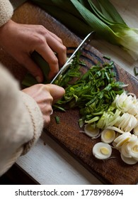 Chopping leeks on wooden chopping board
