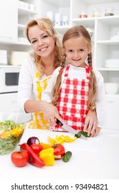 Chopping up vegetables with mom - little girl helping prepare a fresh meal
