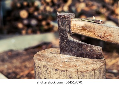 chopping wood with ax. Ax stuck in a log of wood. Old, worn, scratched, sharp ax standing on a wooden, cracked tree stump on a background of chopped wood.