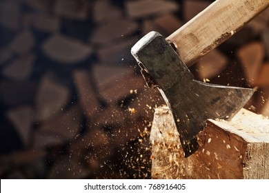 Chopping wood with axe - closeup on flying wooden chips on dark wood stack background, copy space