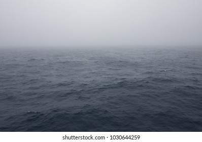 The choppy steel blue water of the South Atlantic Ocean with thick fog overhead. Image has copy space.