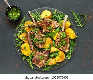 Chops of lamb on bone, with baked potatoes and pesto sauce.