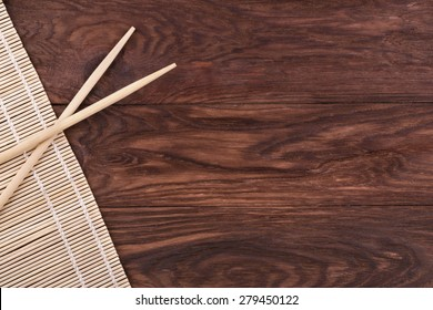 Chopsticks and bamboo napkin on a wooden brown background