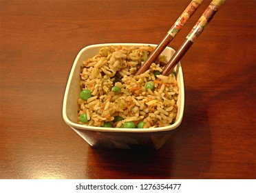Chopsticks in a bowl of Cantonese rice with eggs, peas, carrots and spinaches, on a wooden table.