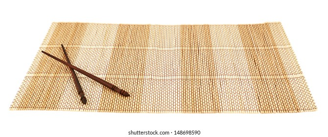 Chopsticks eating utensils over a bamboo mat composition, isolated over white background