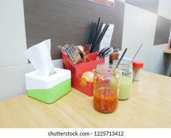 Chopsticks, forks, condiments etc. placed on the table
