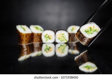 Chopsticks holding roll on dark background made of Nori, Marinated rice, Sesame white, Cucumber. Traditional Japanese cuisine. Sushi menu. Japanese food. Free-space. Close-up.