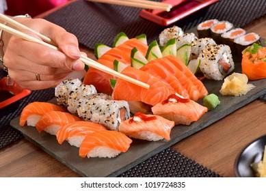 Chopsticks holding a sashimi slice