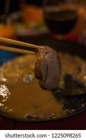 chopsticks holding slice of pork meat up a miso ramen bowl
