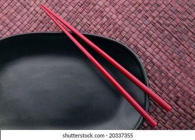 Chopsticks on a black plate