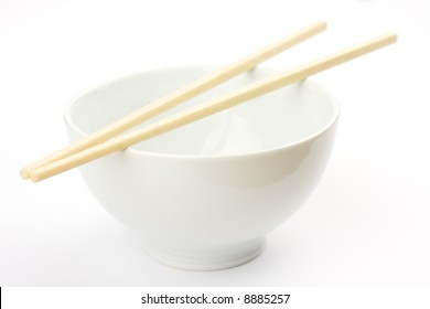 Chopsticks on a white bowl against a white tablecloth