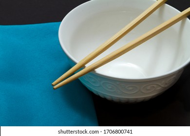 Chopsticks on a white empty rice bowl next to a blue napkin