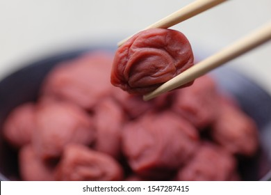 Chopsticks pinching a umeboshi, dried and salt-pickled japanese apricot