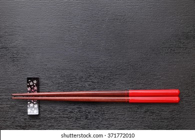 Chopsticks and chopsticks rest on black tray background