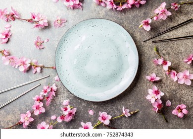 Chopsticks and sakura branches on gray stone background. Japanese food concept. Top view, copy space