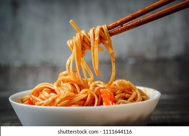 chopsticks take chinese noodles in sweet and sour sauce from plate. Traditional Asian cuisine