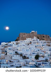 Chora of Astypalaia in blue hour and the full moon rising behind the fortress