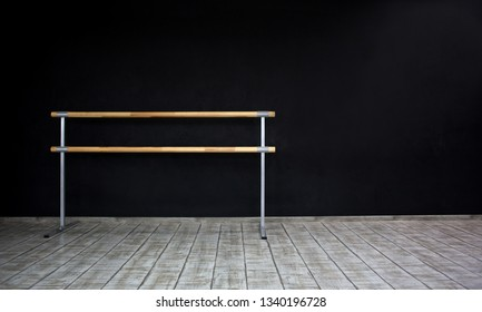Choreography barre. Pilates fitness studio gym room with training dance ballet bar for stretching and splits. Black wall background. Nobody