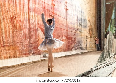 choreography, photography, dancing concept. prima ballerina in elegant blue tutu and warm sport sweatshot practicing fouette in the wings for photographer