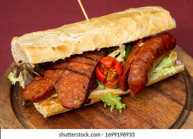 Choripan, a chorizo and chimichurri sandwich popular in South America, grilled Argentine chorizo served with a sauce made of parsley, garlic, chili and oil and vinegar on a crusty bread roll