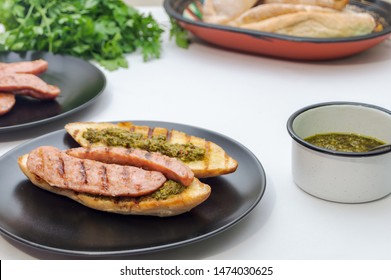 Choripan, south American style chorizo sandwich made with Argentine chorizo sausage with chimichurri, a parsley and olive oil based condiment