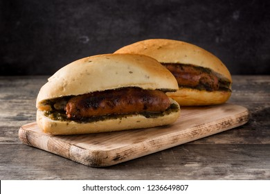 Choripan. Traditional Argentina sandwich with chorizo and chimichurri sauce on wooden table