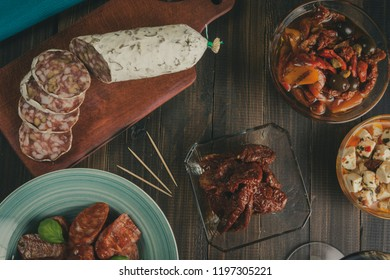 Chorizo and salami sausages on bowls and cutting board with dried tomatoes and olives. Bar ready for new years eve. Vintage effect. Overhead
