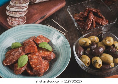 Chorizo and salami sausages on bowls and cutting board with dried tomatoes and olives. Bar ready for new years eve. Vintage effect