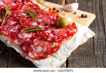 Chorizo sausage and salami, thin cut. spanish salami on the wood background with spices, paprika, pepper. Spicy food. Chili.