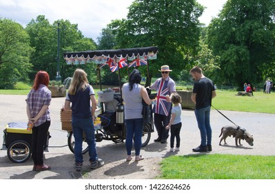 Chorley, Lancashire/UK - June 9th 2016: Astley Hall, people and children queuing at an outdoor ice cream vendor with cart at a historic house and park on a sunny day