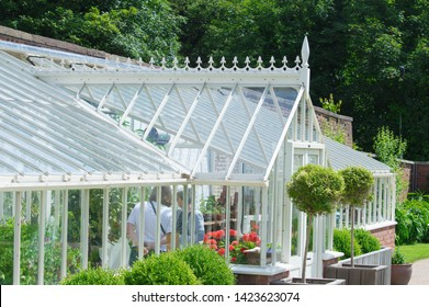 Chorley, Lancashire/UK - June 9th 2019: Astley Hall, a summery image of two women inside a Victorian style greenhouse, white with glass, in walled garden with bay trees and greenery