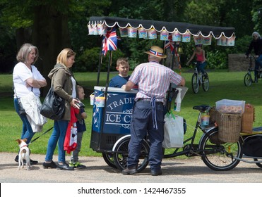 Chorley, Lancashire/UK - June 9th 2019: people, women and children, queuing at an ice cream vendor with tricycle cart and union jack bunting at a park on a bright and sunny day